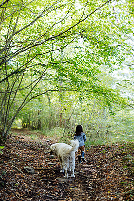 Rear view of child with dog in the forest - p300m2144748 by Sofie Delauw