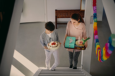 High angle view of siblings carrying birthday cake and gift box while climbing up steps at home - p426m1580231 by Maskot