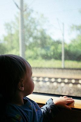 Baby boy gazing out train window - p795m2223682 by JanJasperKlein