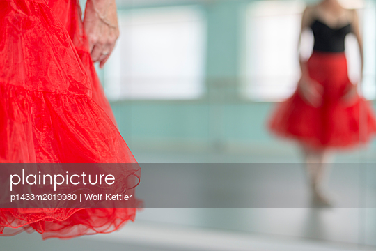 Female ballet dancer in red and black tutu with her own reflection in the mirror. - p1433m2019980 by Wolf Kettler