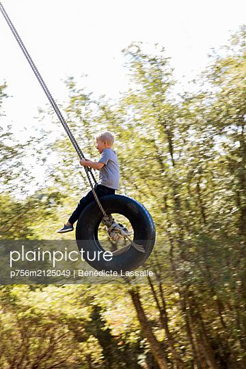Boy has fun in a tire swing - p756m2125049 by Bénédicte Lassalle