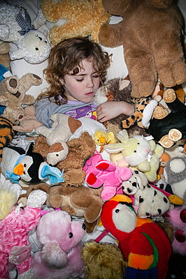 Girl amidst many cuddly toys - p1057m1222768 by Stephen Shepherd