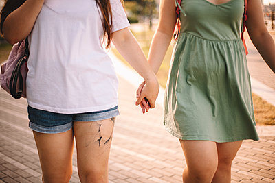 Midsection of lesbian couple holding hands while walking in city - p1166m2212435 by Cavan Images