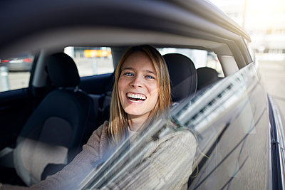 Portrait of laughing young woman sitting in car - p300m1581522 von Philipp Nemenz