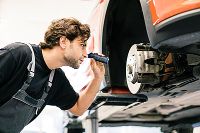 Car mechanic in a workshop working at car - p300m2166814 by Robijn Page