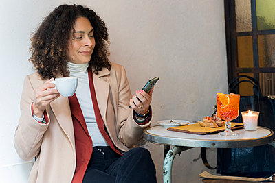 Woman looking at cell phone in a cafe - p300m2170169 by Francesco Morandini