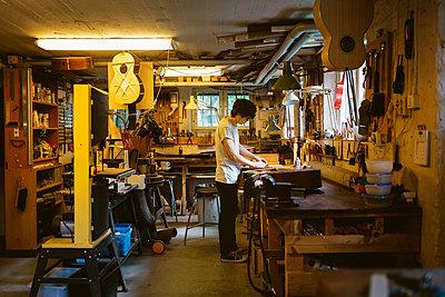 Craftsman working in guitar making workshop - p352m2041534 by Folio Images