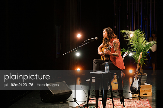 Female musician playing guitar and singing on stage - p1192m2123178 by Hero Images