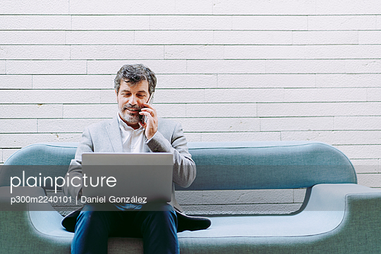 Businessman talking through mobile phone using laptop while sitting on sofa against wall in hotel - p300m2240101 by Daniel González