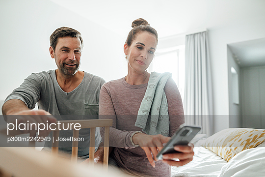 Mature woman with man taking photograph of crib in bedroom - p300m2242949 by Joseffson
