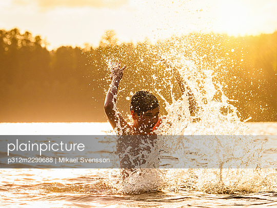 Boy in sea splashing water - p312m2299688 by Mikael Svensson