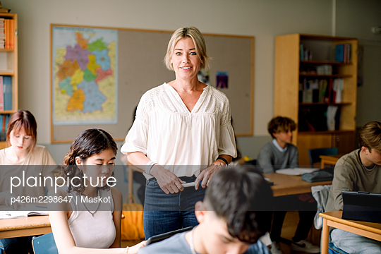 Smiling female professor standing by teenage girl in classroom - p426m2298647 by Maskot