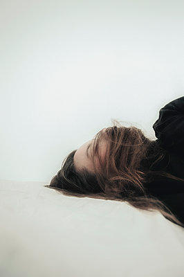Woman lying down with hair over face - p1047m1502578 by Sally Mundy