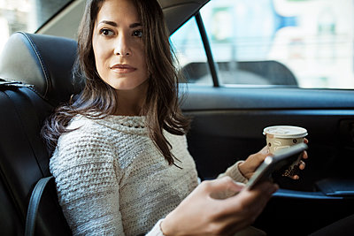 Young woman holding disposable glass and smart phone in taxi - p1166m1144711 by Cavan Images