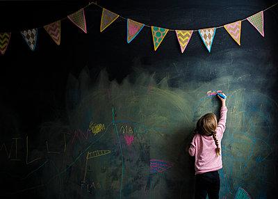 Rear view of girl drawing on blackboard - p1166m1474022 by Cavan Images