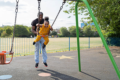 Father with happy daughter swinging on a playground - p300m2154836 by Francesco Buttitta