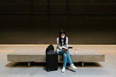 Female passenger reading book while sitting at metro station - p300m2240698 by Ezequiel Giménez