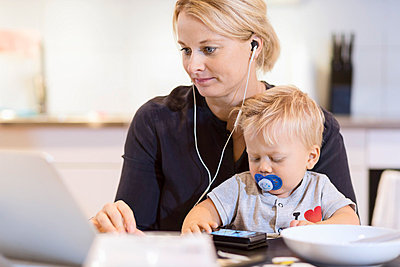 Baby boy using smart phone while mother listening music on laptop at table - p426m1017821f by Maskot
