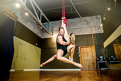 Caucasian acrobats hanging from ropes in studio - p555m1412619 by Inti St Clair