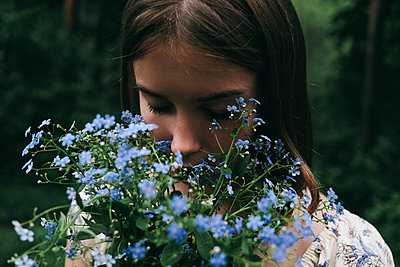 Caucasian woman smelling flowers - p555m1531615 by Vladimir Serov