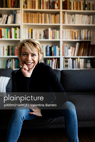 Portrait of happy mature woman sitting on couch at home - p300m2144803 by Valentina Barreto