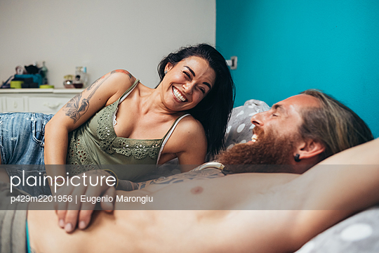 Bearded tattooed man with long brunette hair and woman with long brown hair lying on a bed, smiling at each other. - p429m2201956 by Eugenio Marongiu