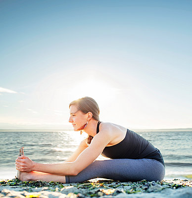 Woman practicing seated forward bend at beach against sky - p1166m1227819 by Cavan Images