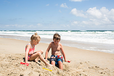 Siblings playing with sand at beach against sky during sunny day - p1166m1404030 by Cavan Images
