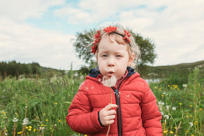 Portrait of girl blowing dandelion while standing on field - p1166m1543844 by Cavan Images