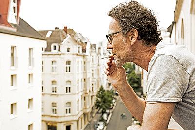 Man smoking on balcony - p300m1156685 by Jo Kirchherr