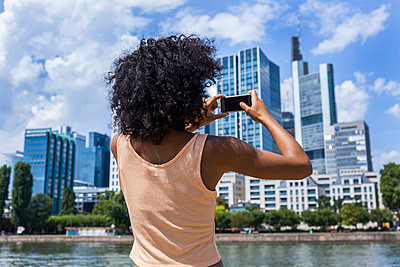 Germany, Frankfurt, back view of young woman with curly hair taking photo with smartphone - p300m2030340 by Tom Chance