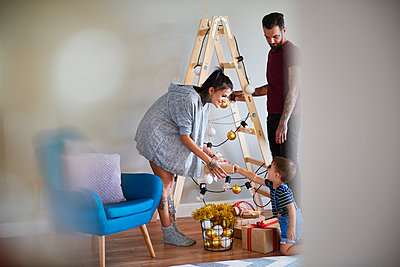Modern family at home at Christmas time using ladder as Christmas tree - p300m2041633 by gpointstudio