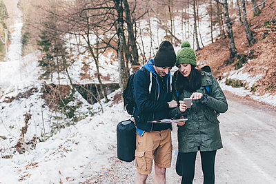 Hiking couple on snowy forest road looking at smartphone, Monte San Primo, Italy - p429m1448264 by Eugenio Marongiu