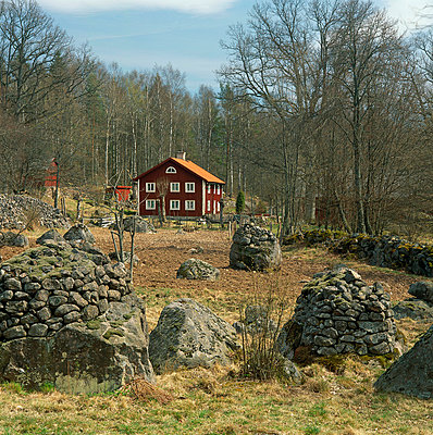 Red farmhouse and piles of stone - p4692127 by Peter Gerdehag