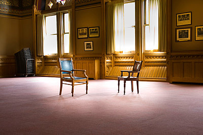 Two old-fashioned style business chairs in a large empty room - p6070659 by Peter Glass
