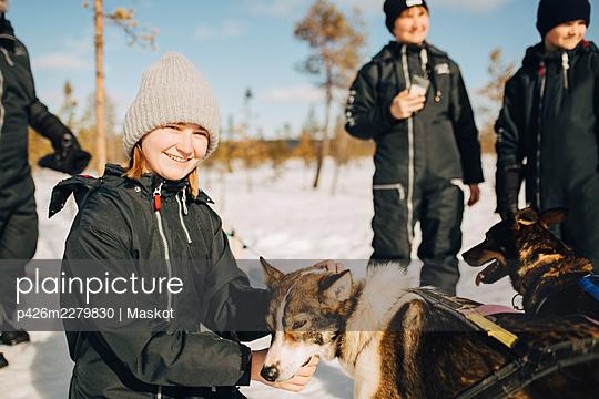 Portrait of smiling teenage girl stroking husky dog during winter - p426m2279830 by Maskot