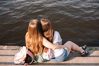 Back view of lesbian couple embracing while sitting on steps by river - p1166m2212420 by Cavan Images