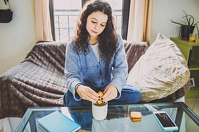 young woman with cookies and coffee at breakfast sitting on the sofa - p1166m2255419 by Cavan Images