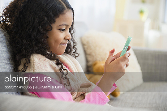 Mixed race girl texting with cell phone on sofa - p555m1413065 by JGI/Jamie Grill