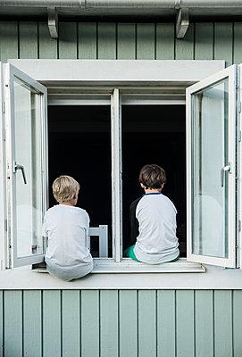 Boys sitting on window - p312m1187660 by Helen Karlsson