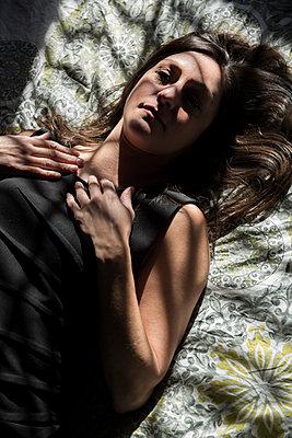 Junge Frau liegt in ihrem Bett - p397m1556577 von Peter Glass