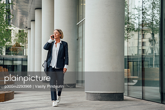 Female professional talking on mobile phone while walking in office park - p300m2293968 by Vasily Pindyurin