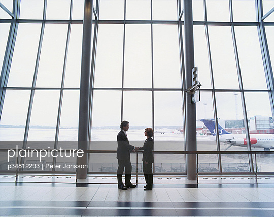 Two business executives shaking hands at an airport