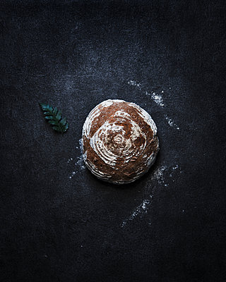 Overhead view of homemade bread loaf on table - p1166m1415177 by Cavan Images