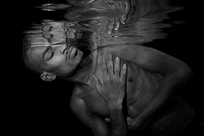 African American male underwater - p1554m2158936 by Tina Gutierrez