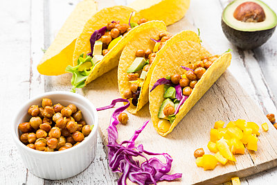 Vegetarian tacos filled with in curcuma roasted chick peas, yellow paprika, avocado, salad and red cabbage - p300m2012862 von Larissa Veronesi