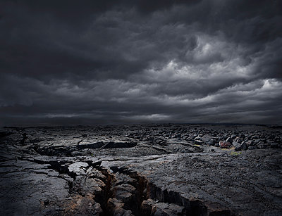 Storm clouds over dry rocky landscape - p555m1454219 by Chris Clor