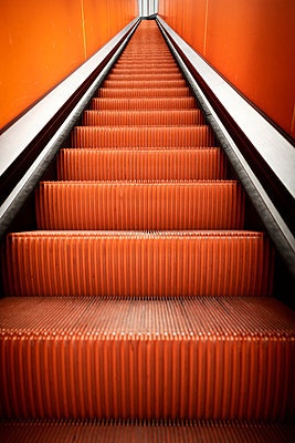 Orange-coloured moving stairs - p1092m2054258 by Rolf Driesen