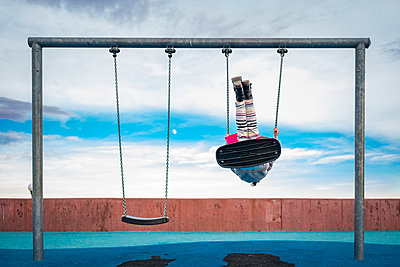 Playful girl swinging against cloudy sky at playground - p1166m2011540 by Cavan Images