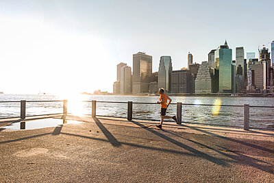 USA, Brooklyn, man jogging in front of Manhattan skyline in the evening - p300m1205680 by Uwe Umstätter
